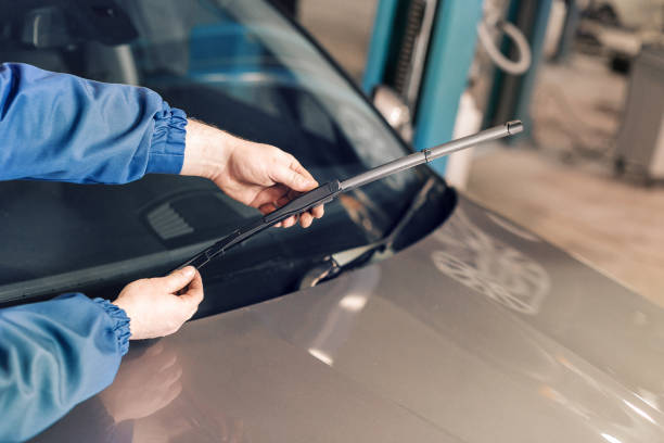 Technician is changing windscreen wipers on a car station. stock photo