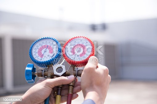 istock Technician is checking air conditioner ,measuring equipment for filling air conditioners. 1004830680