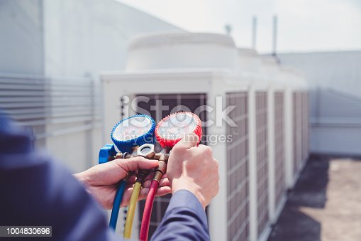istock Technician is checking air conditioner ,measuring equipment for filling air conditioners. 1004830696