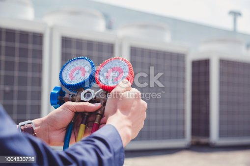 istock Technician is checking air conditioner ,measuring equipment for filling air conditioners. 1004830728