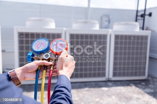 istock Technician is checking air conditioner ,measuring equipment for filling air conditioners. 1004830810