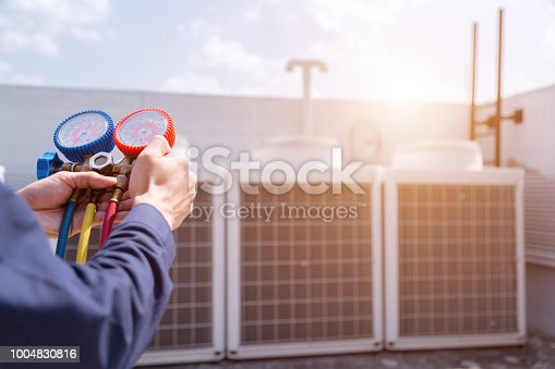 istock Technician is checking air conditioner ,measuring equipment for filling air conditioners. 1004830816