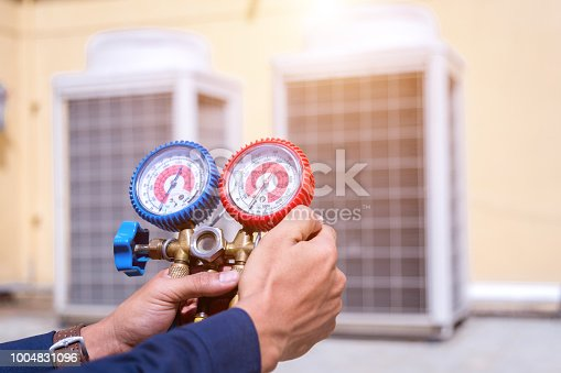 istock Technician is checking air conditioner ,measuring equipment for filling air conditioners. 1004831096
