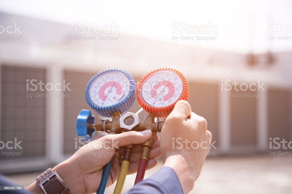 Technician is checking air conditioner ,measuring equipment for filling air conditioners. stock photo