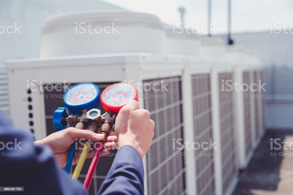 Technician is checking air conditioner ,measuring equipment for filling air conditioners. royalty-free stock photo