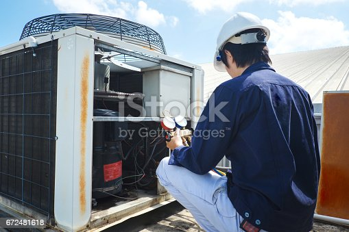 istock Technician is checking air conditioner 672481618