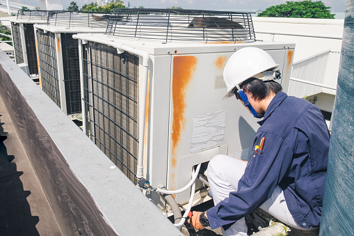 istock Technician is checking air conditioner 672495312