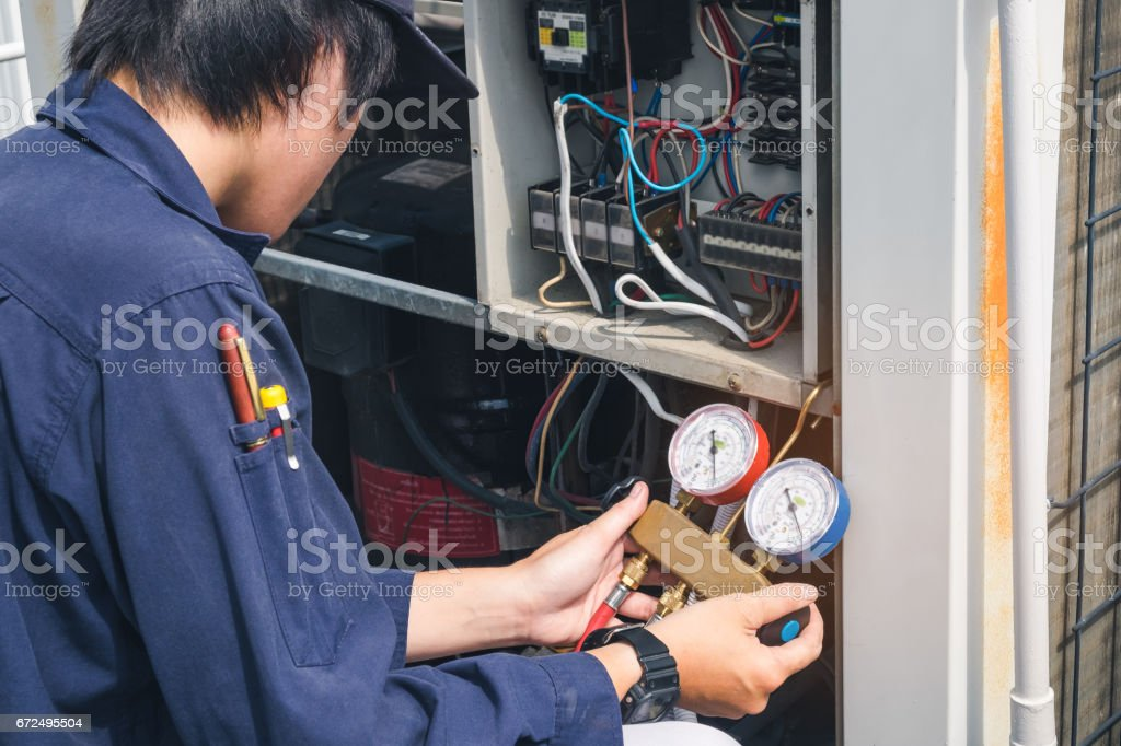 Technician is checking air conditioner stock photo