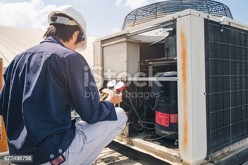 istock Technician is checking air conditioner 672495756