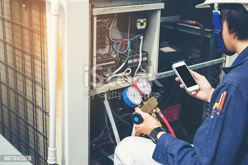istock Technician is checking air conditioner 697542078