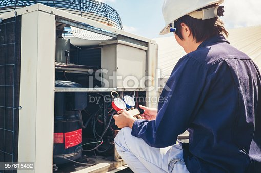 istock Technician is checking air conditioner 957616492