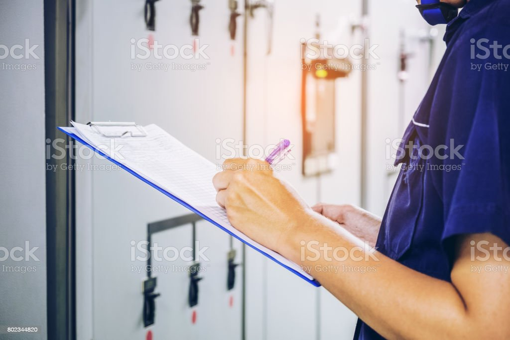 Technician is recording data Voltage or current in control panel of power plants stock photo