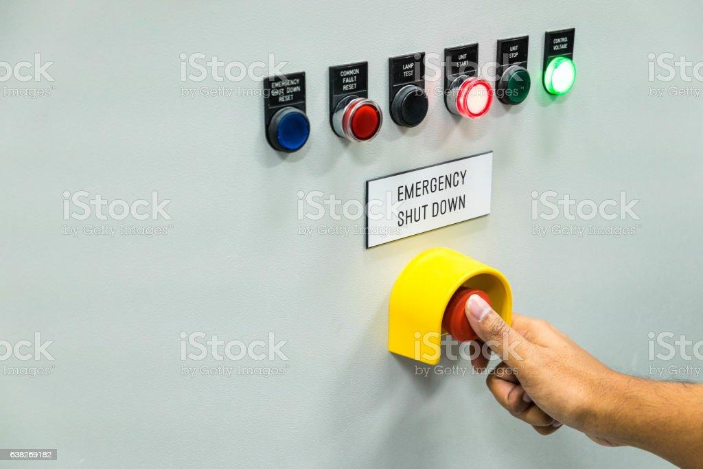 Technician is turning on emergency shutdown button on stock photo