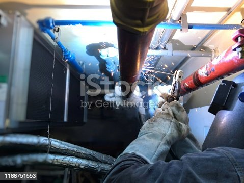 Technician is welding the black steel pipe after the Freezing pipe because cannot shut off valve.Technician working on Hospital Site.