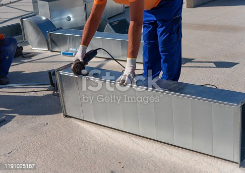 895571294 istock photo HVAC technician is working on a roof of new industrial building. Close-up view of the young technician repairing an air duct with the angle grinder. HVAC worker cutting ductwork with an angle grinder. 1191025187