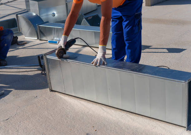 HVAC technician is working on a roof of new industrial building. Close-up view of the young technician repairing an air duct with the angle grinder. HVAC worker cutting ductwork with an angle grinder. stock photo