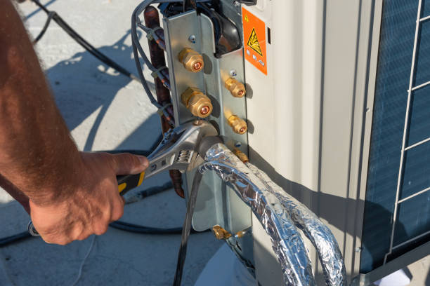 HVAC technician is working on air conditioner units on a roof of new industrial building.Technician hand using fix wrench to tighten outdoor unit of air condition. Man holds a wrench in his hand. stock photo
