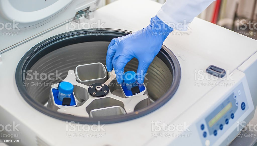 Technician loading a sample to centrifuge machine stock photo