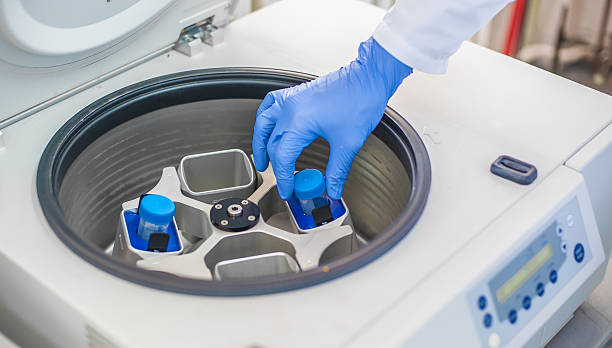 Technician loading a sample to centrifuge machine - foto stock