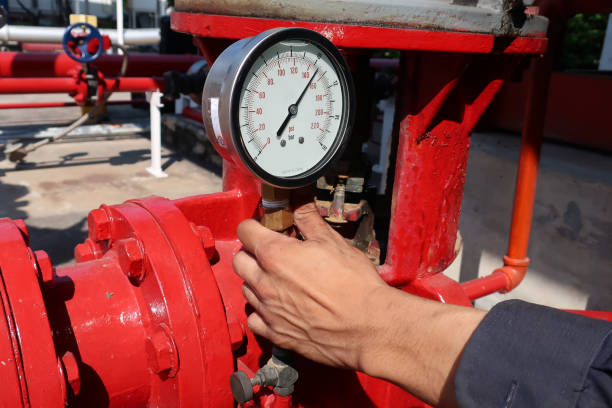 technician man holding gauge for check pressure of pipe in the industry