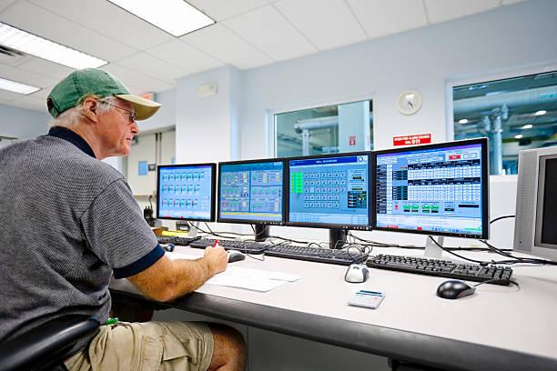 Technician Monitoring in Control Room stock photo