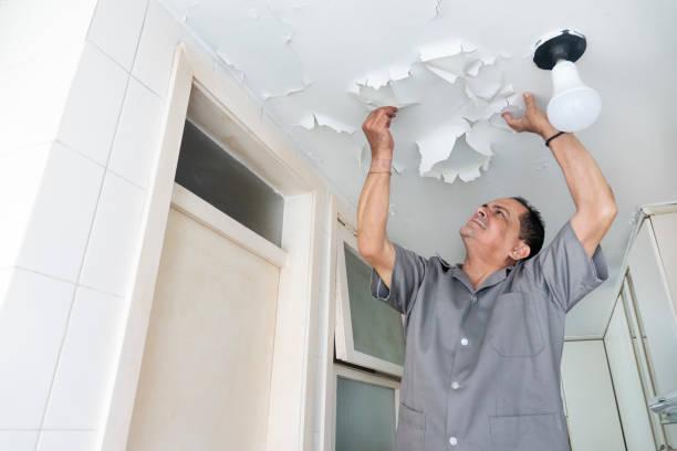 Technician observes peeling kitchen ceiling