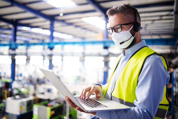 Technician or engineer with protective mask and laptop working in industrial factory. stock photo