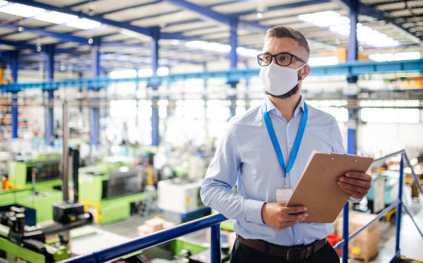 Technician or engineer with protective mask working in industrial factory, standing. stock photo