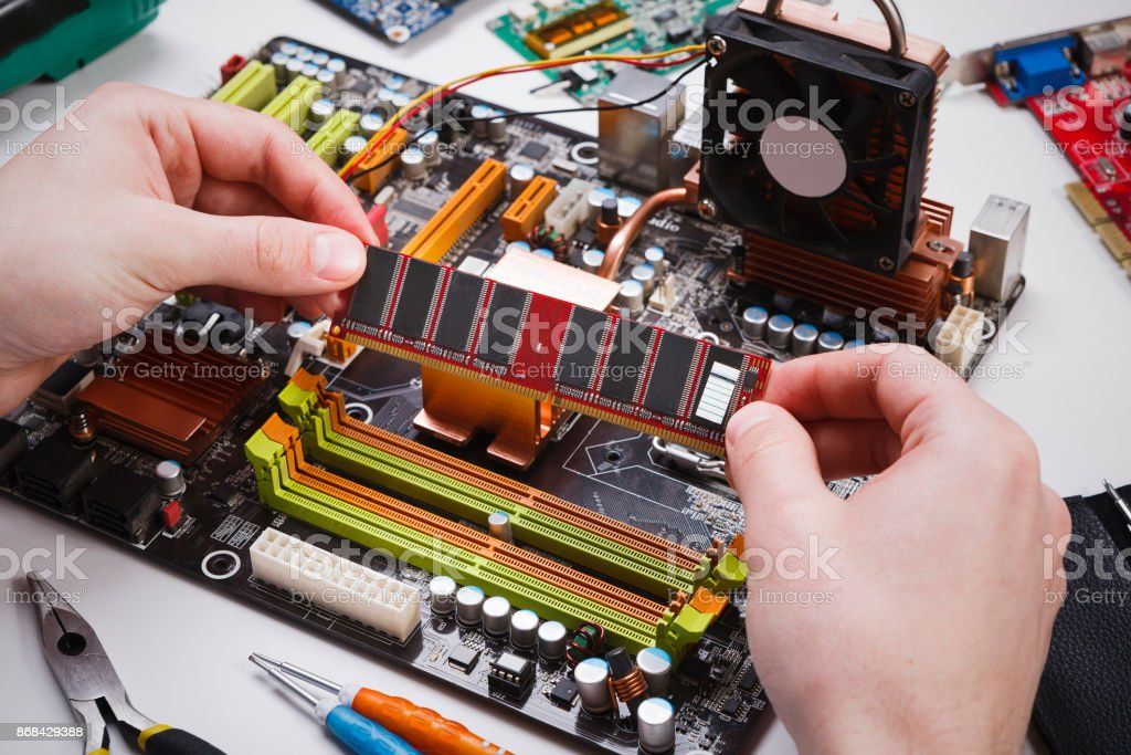 Technician plug in microprocessor to motherboard stock photo