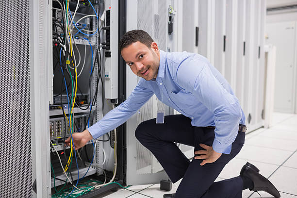 Technician plugging cable into server stock photo