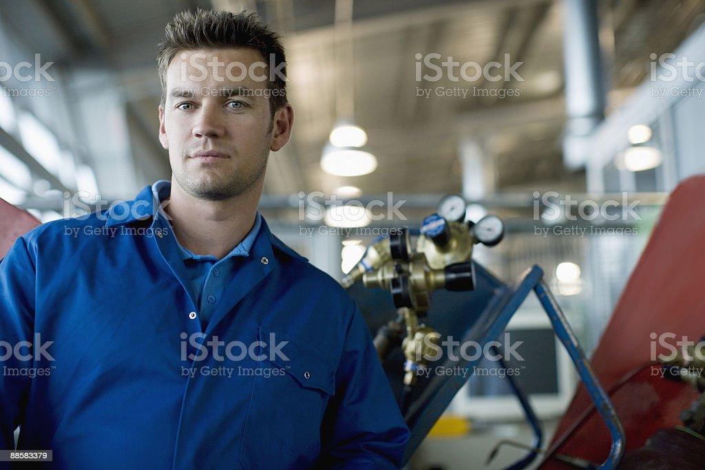 Technician posing in auto shop stock photo