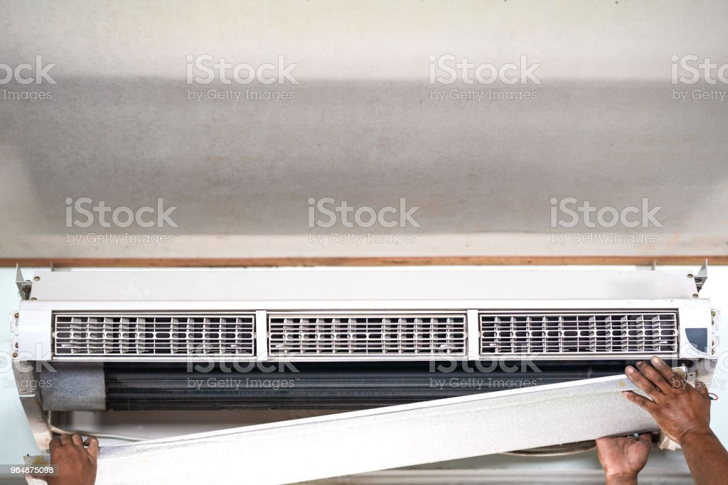 Technician repair and clean air conditioner on summer stock photo