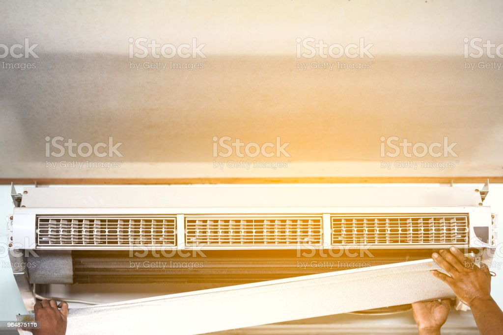 Technician repair and clean air conditioner on summer royalty-free stock photo