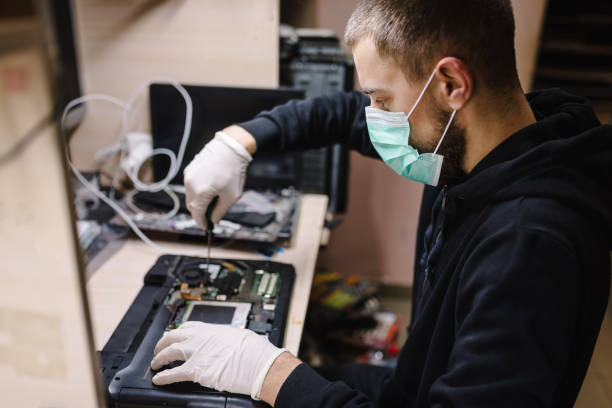 Technician repairing a laptop in the lab. Concept of repair computer, electronic, upgrade, technology.  Coronavirus. Man working, wearing protective mask in workshop.