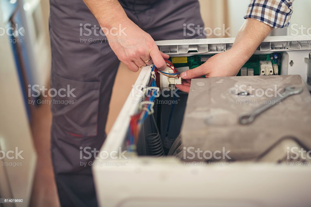 Technician repairing a washing machine stock photo