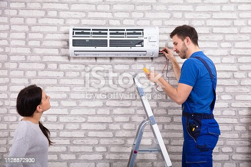 istock Technician Repairing Air Conditioner With Digital Multimeter 1128872930