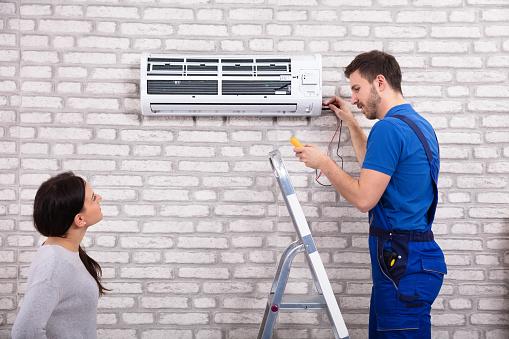 istock Technician Repairing Air Conditioner With Digital Multimeter 1128872930