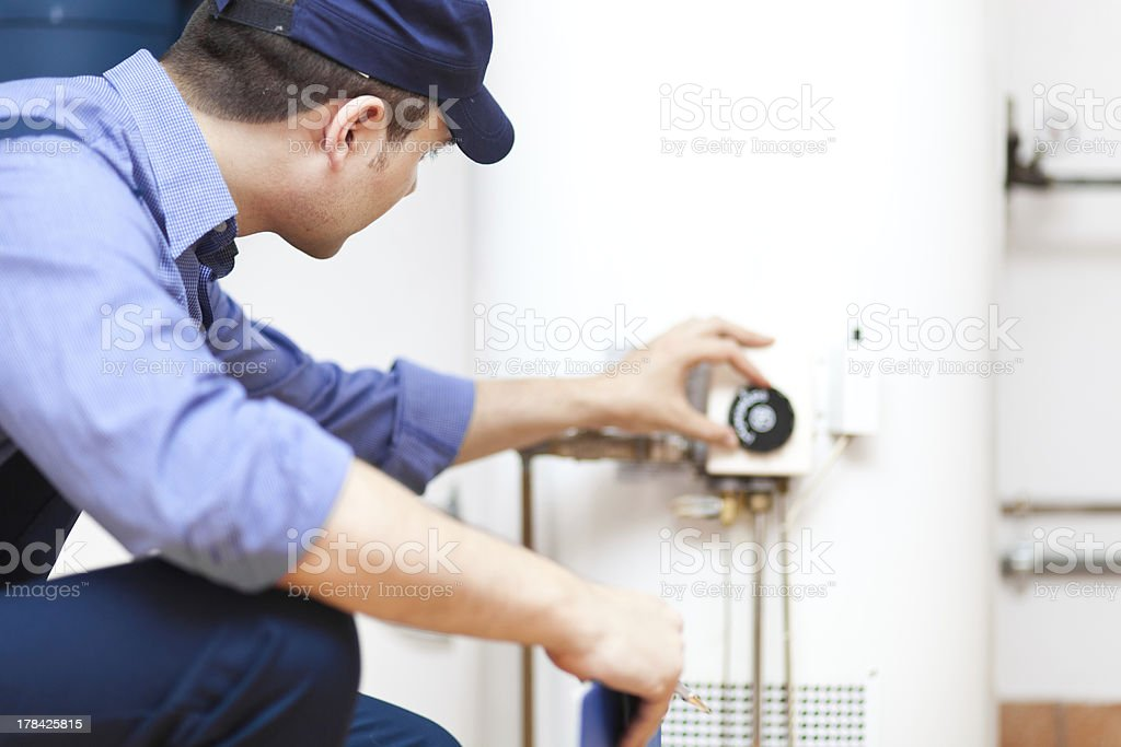 Technician repairing an hot-water heater royalty-free stock photo