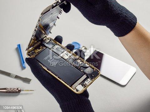 istock Technician repairing broken smartphone on desk 1094496306