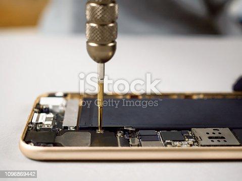 istock Technician repairing broken smartphone on desk 1096869442