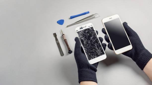 technik naprawia uszkodzony smartfon na biurku - naprawiać zdjęcia i obrazy z banku zdjęć
