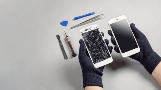 techniker reparieren defekte smartphone auf schreibtisch - reparieren stock-fotos und bilder