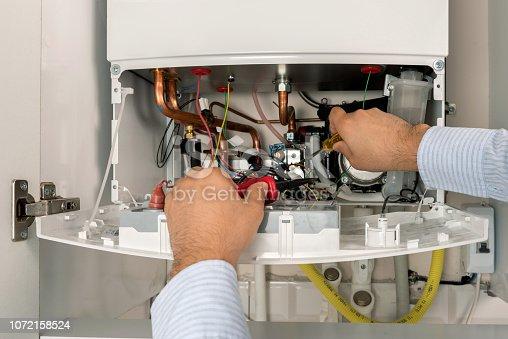 istock Technician repairing combi Gas Boiler 1072158524