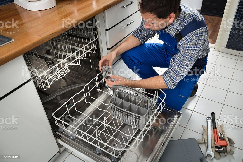 Technician Repairing Dishwasher stock photo