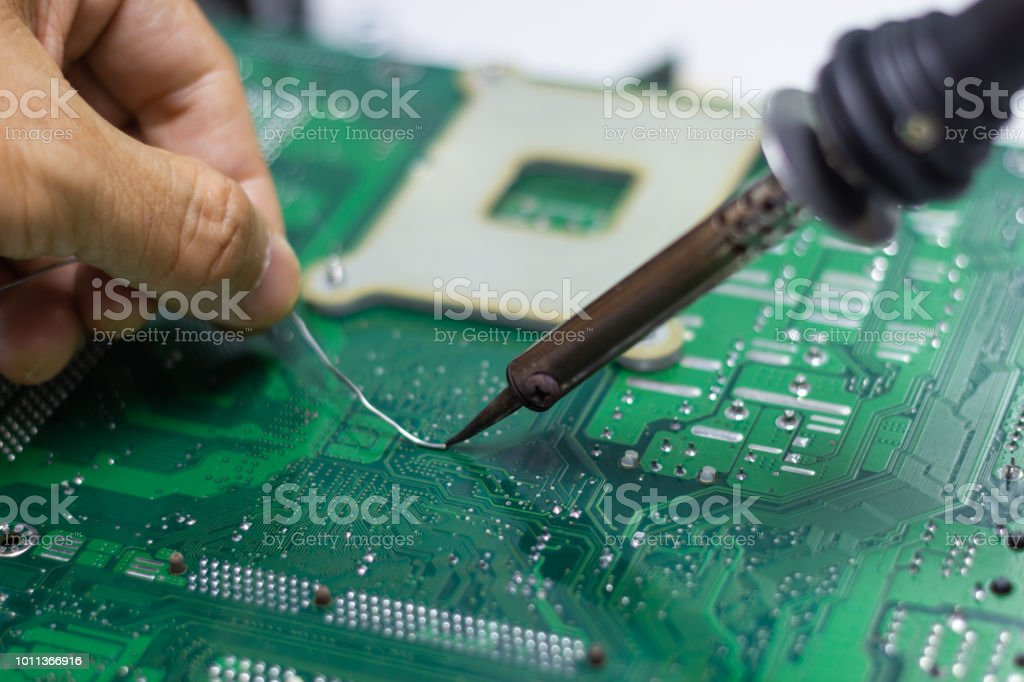 technician repairing electronic of the computers circuit board bytechnician repairing electronic of the computer\u0027s circuit board by soldering irons, stock image