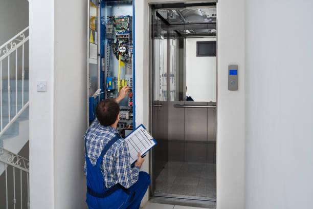 Technician Repairing Elevator stock photo