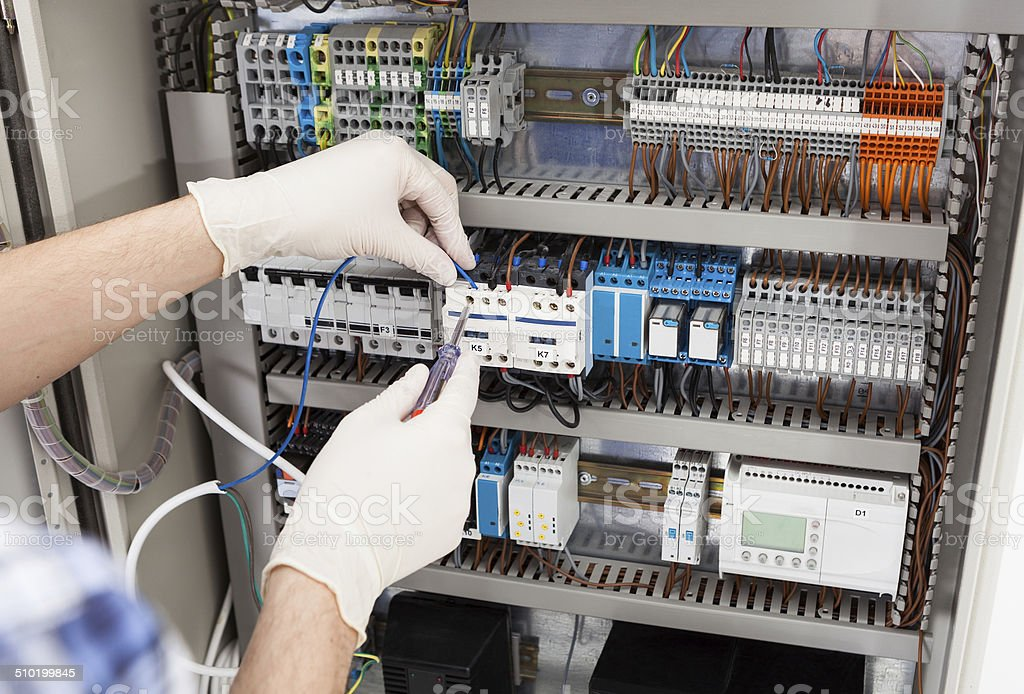 Technician Repairing Fusebox stock photo