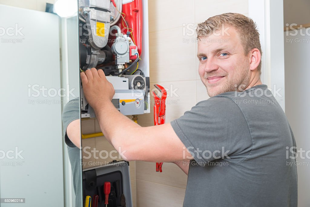 Technician repairing Gas Furnace stock photo