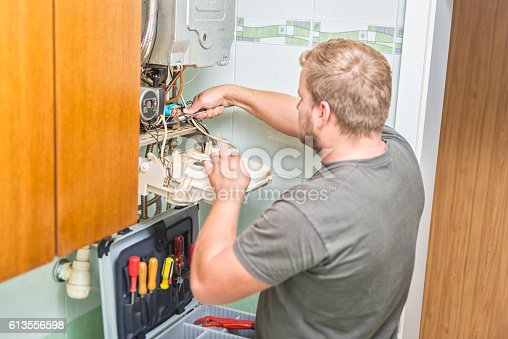 istock Technician repairing Gas Furnace 613556598