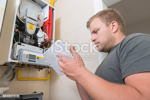 istock Technician repairing Gas Furnace using digital tablet 534307318